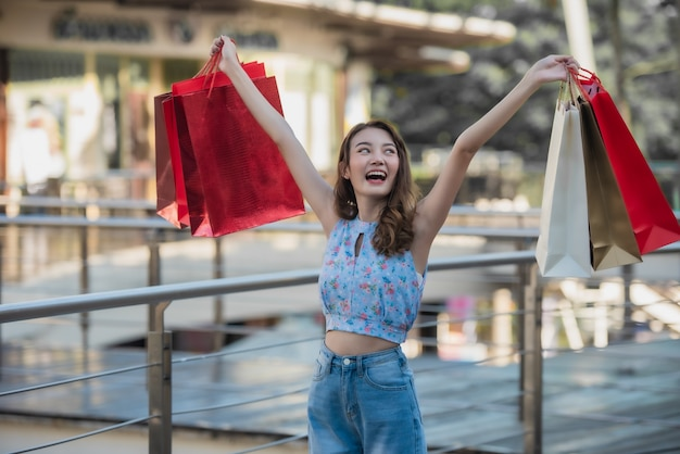 Asiatin, die einkaufstaschen und angehobene hände hochhält Premium Fotos