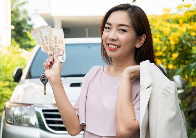 Asiatin, die geld und autoschlüssel gegen ein auto hält. versicherung, darlehen und finanzen Premium Fotos