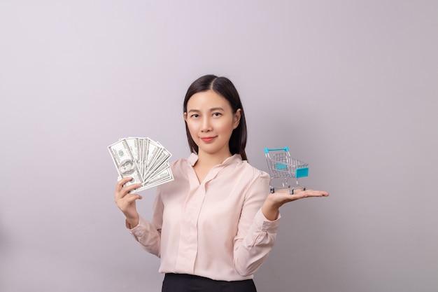 Asiatin, die in der hand geld und warenkorb hält Premium Fotos