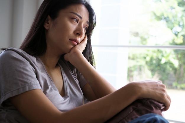 Asiatin, die innerhalb des hauses heraus betrachtet das fenster sitzt. frau verwirrt, enttäuscht, traurig und verärgert Premium Fotos