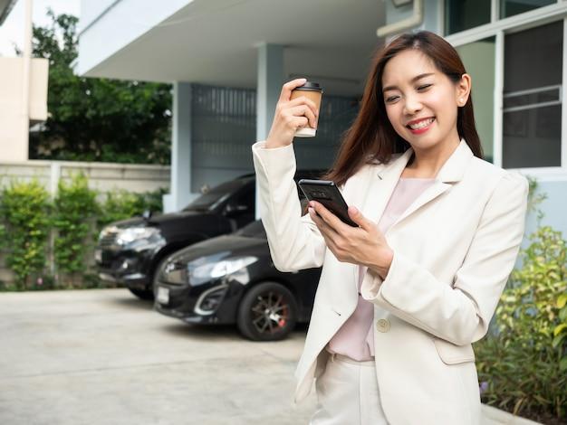 Asiatin, die kaffeetasse hält und smartphone bei der stellung vor haus verwendet. Premium Fotos