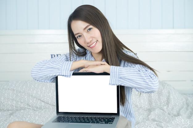 Asiatin, die leeren laptop-computer schirm in ihrem schlafzimmer lächelt und zeigt. Premium Fotos