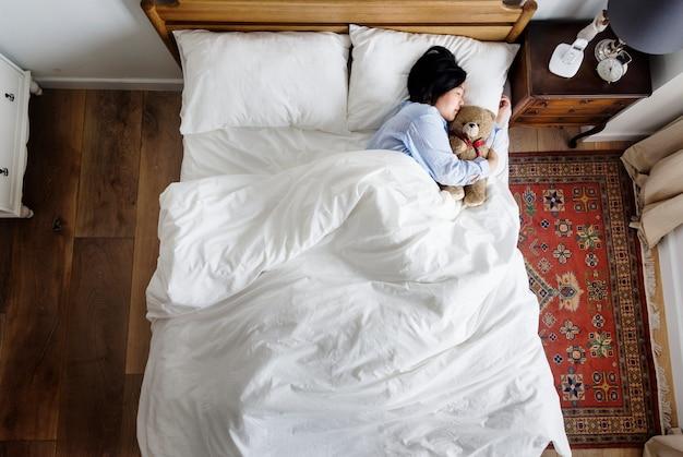Asiatin, die mit einer puppe schläft Premium Fotos