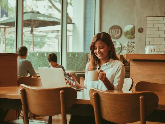 Asiatin, die mit laptop im kaffeeshopcafé arbeitet Premium Fotos