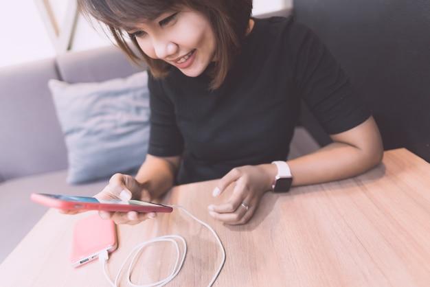 Asiatin, die mit smartphone beim laden mit energiebank glücklich sich fühlt. Premium Fotos