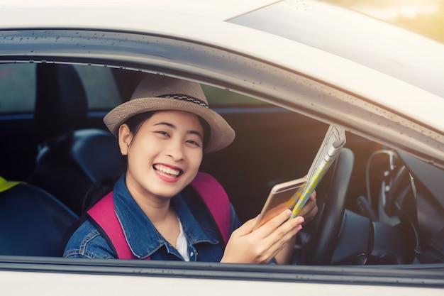 Asiatin, die smartphone und karte zwischen dem fahren des autos auf autoreise verwendet Premium Fotos