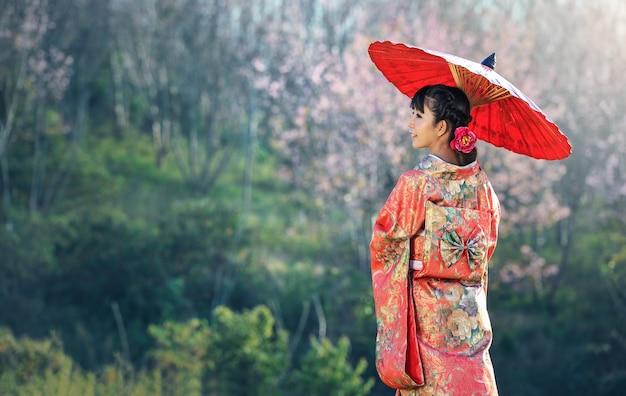 Asiatin, die traditionellen japanischen kimono, kirschblüte-hintergrund trägt Premium Fotos