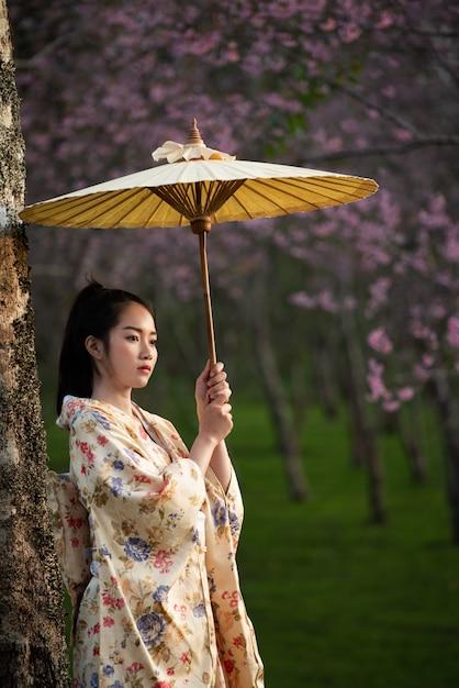 Asiatin, die traditionellen japanischen kimono mit kirschblüte trägt Premium Fotos