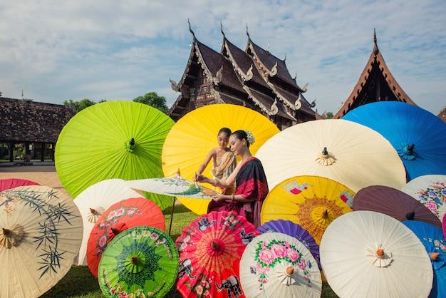 Asiatin, die traditionellen kostümmalereiregenschirm, lanna-art nord-chiangmai thailand trägt Premium Fotos
