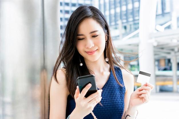 Asiatin, die zahlung mit kreditkarte unter verwendung der handyanwendung leistet Premium Fotos