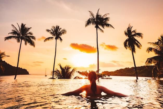 Asiatin entspannen sich im pool auf strand Premium Fotos