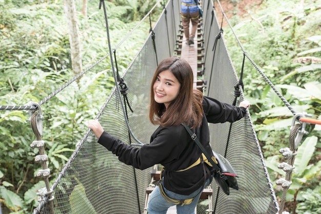 Asiatin genießen, auf hängende brücke im wald, doi tung zu reisen Premium Fotos