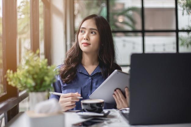 Asiatin hat ein notizbuch, eine tablette zu tragen und denkt mit einem lächeln in der kaffeestube. Premium Fotos
