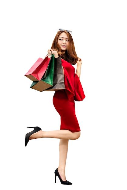 Asiatin in der roten kleidung und in der sonnenbrille, die einkaufstaschen tragen Premium Fotos