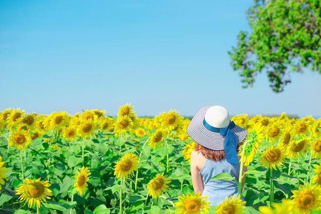 Asiatin mit hut auf einem gebiet von blumen, genießend im sonnenblumenfeld Premium Fotos