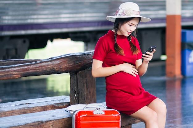 Asiatin schwanger im roten kleid, das rotes gepäck und blick auf das smartphone mit einem roten koffer trägt Premium Fotos
