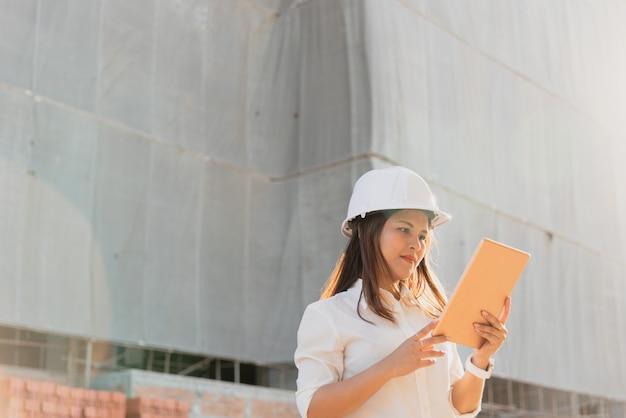 Asiatinbauingenieur mit weißer schutzhelmbesuchbaustelle. Premium Fotos