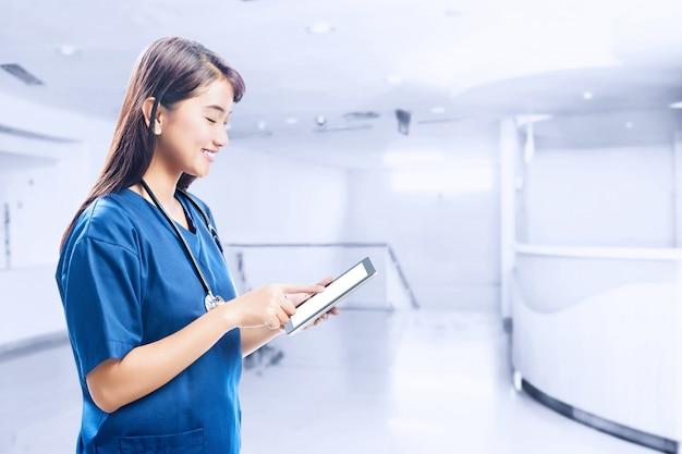Asiatinkrankenschwester mit stethoskop unter verwendung der tablette Premium Fotos