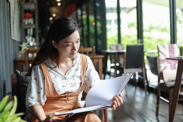 Asiatinlesebuch und lächeln und glückliche entspannung in einer kaffeestube Premium Fotos