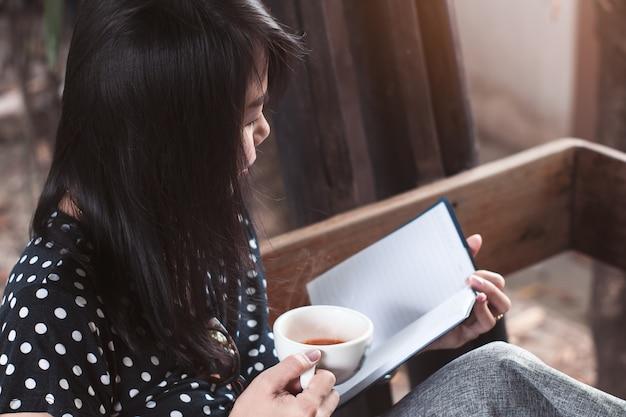 Asiatinlesebuch und trinkender kaffee oder tee mit glücklichem Premium Fotos