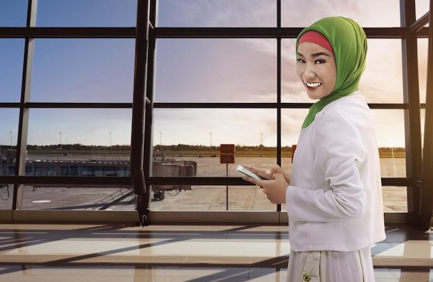 Asiatinmoslem, der das telefon hält Premium Fotos