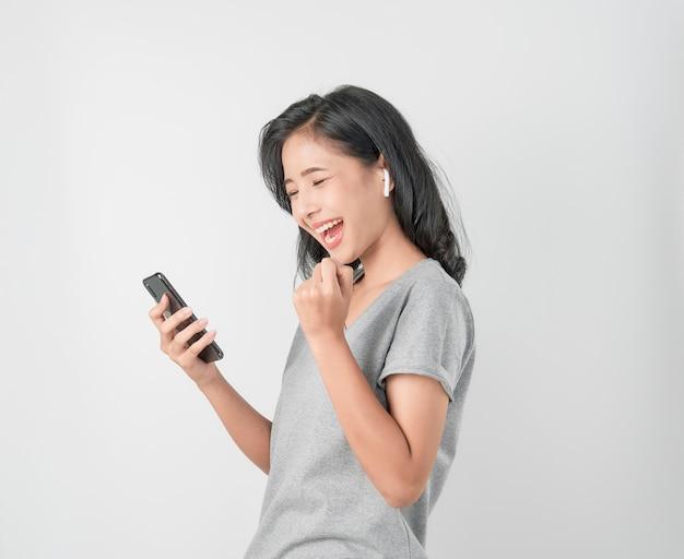 Asiatinnen des glücklichen lächelns hören musik von den weißen kopfhörern. und mit den händen berühren, um verschiedene funktionen zu nutzen, fröhliche stimmung auf blau. Premium Fotos