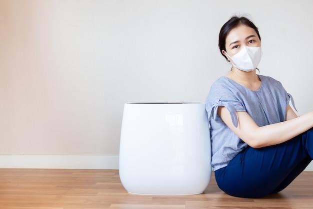 Asiatinnen, die ein gesundheitsproblem von der luftverschmutzung in ihrem haus hat, das neben der luftreinigermaschine im wohnzimmer auf dem bretterboden sitzt Premium Fotos