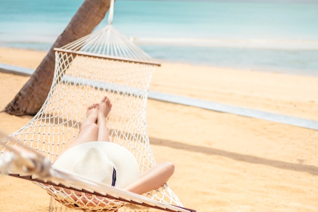 Asiatinnen, die in den hängemattensommerferien auf strand sich entspannen Premium Fotos