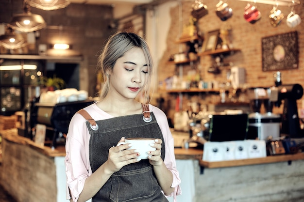 Asiatinnen, die kaffeetasse am café halten Premium Fotos