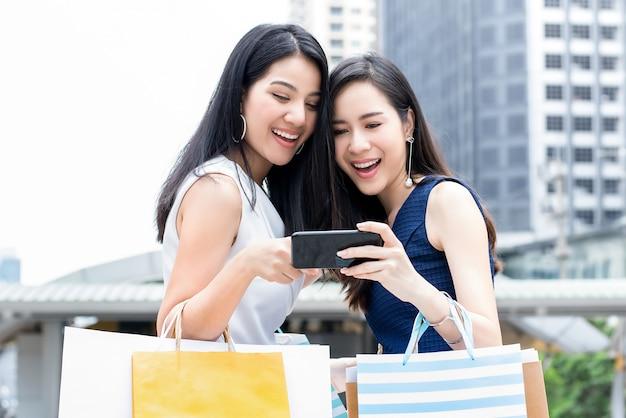 Asiatinnen genießen, über smartphone online zu kaufen, während sie in die stadt reisen Premium Fotos