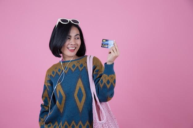 Asiatinnen mit der sonnenbrille, rosa tasche und kopfhörer, die kreditkarten zeigen. Premium Fotos