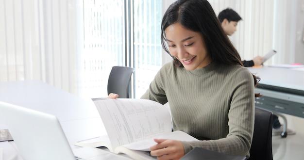 Asiatinnen studentinnen lächeln und lesebuch und unter verwendung des notizbuches Premium Fotos