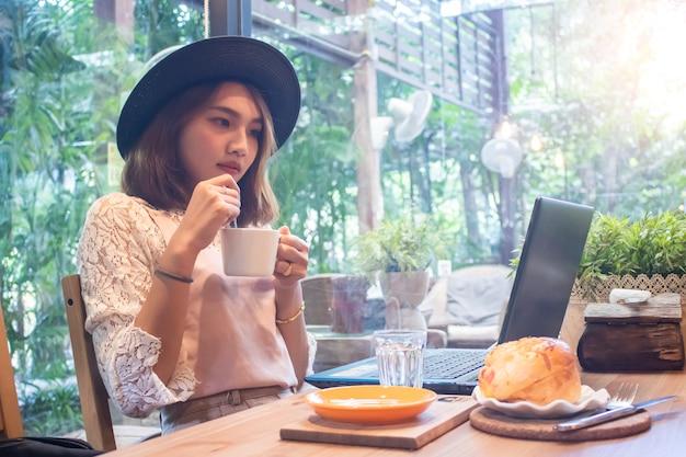 Asiatinnen, welche die kaffeetasse schaut laptop im café halten Premium Fotos