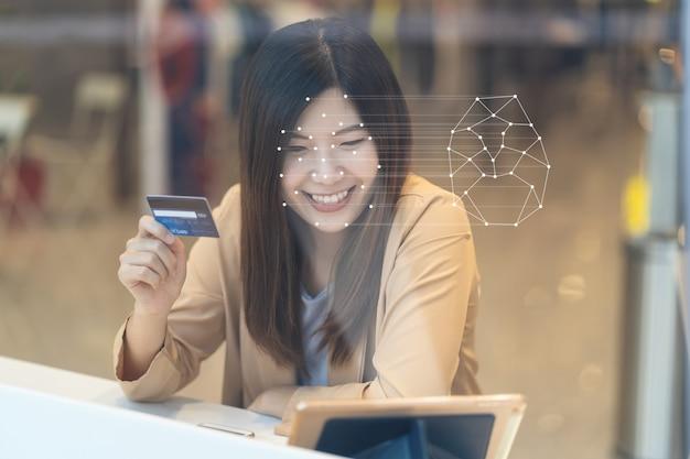 Asiatinnen, welche die technologietablette für zugangskontrolle durch gesichtserkennung verwenden Premium Fotos