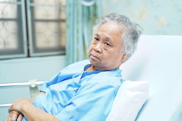 Asiatinpatient, der auf bett im krankenhaus sitzt. Premium Fotos