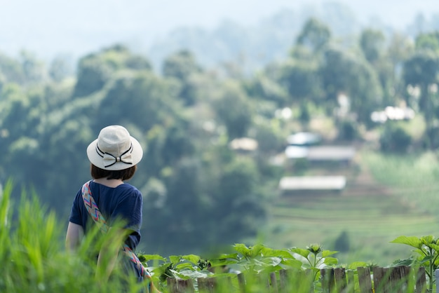 Asiatinreisender, der erstaunliche berge und himmel, reisefeiertags-entspannungskonzept betrachtet. Premium Fotos