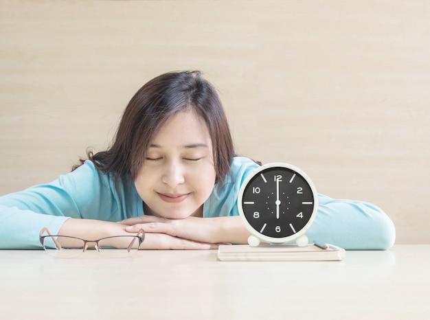 Asiatinschlaf vorbei gelogen auf schreibtisch mit glücklichem gesicht in der ruhezeit vom lesebuch mit uhr Premium Fotos