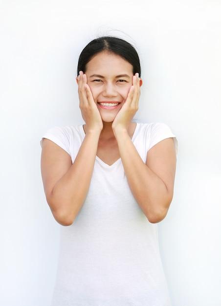 Asiatint-shirt, das ihre backe mit lächeln auf weißem hintergrund steht und berührt Premium Fotos