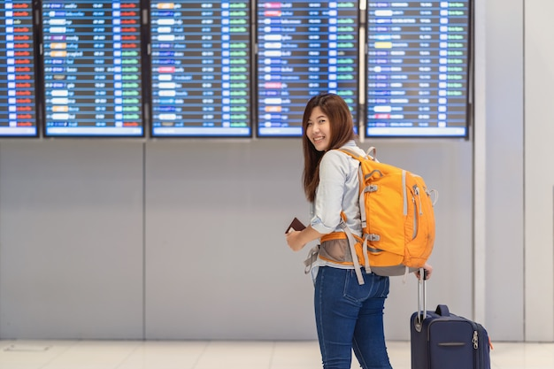 Asiatinwanderer oder -reisender mit gepäck mit pass gehend über den flugeber Premium Fotos
