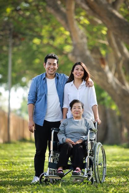 Asiatische ältere frau, die auf dem rollstuhl mit glücklichem lächelngesicht der familie auf dem grünen park sitzt Premium Fotos