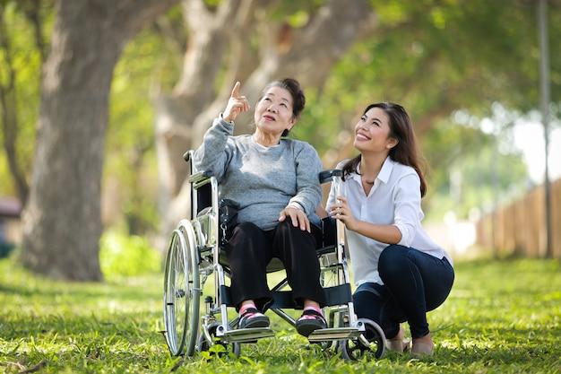 Asiatische ältere frau, die auf dem rollstuhl mit ihrem glücklichen lächelngesicht der tochterfamilie auf dem grünen park sitzt Premium Fotos