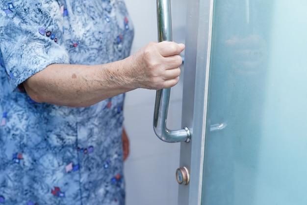 Asiatische ältere frau öffnet badezimmertür von hand im krankenhaus Premium Fotos