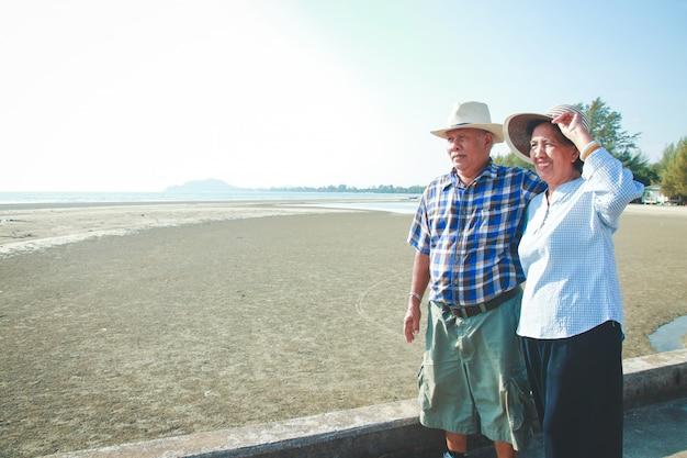 Asiatische ältere paare, die durch das meer sich umarmen glücklich nach ruhestand Premium Fotos