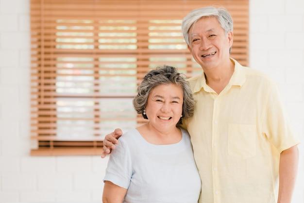 Asiatische ältere paare, die glücklichem lächeln zur kamera lächeln und schauen, während im wohnzimmer zu hause sich entspannen. Kostenlose Fotos
