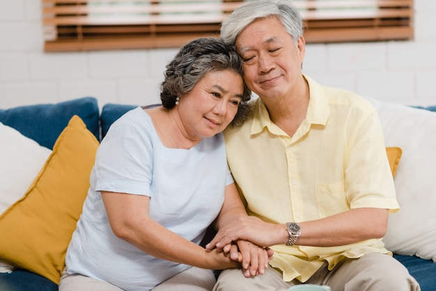 Asiatische ältere paare, die ihre hände beim zusammennehmen im wohnzimmer, glücklichen anteil der paare und unterstützung sich liegend auf sofa zu hause liegen halten. Kostenlose Fotos