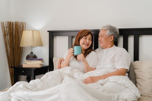 Asiatische ältere paare, die zu hause auf bett sprechen. asiatische ältere chinesische großeltern, ehemann und frau, die glücklich sind, trinken kaffee, nachdem sie beim auf bett im konzept des schlafzimmers zu hause morgens liegen aufgewacht sind. Kostenlose Fotos