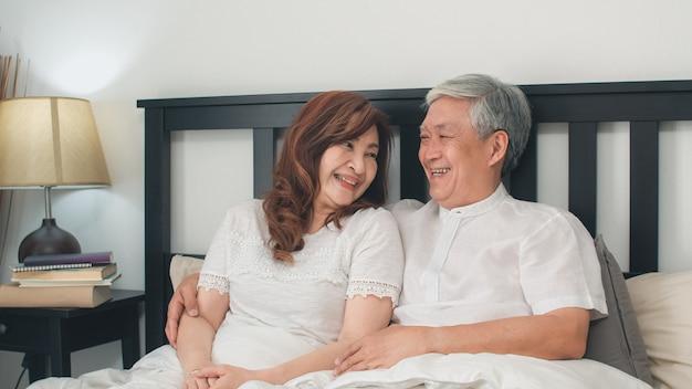 Asiatische ältere paare, die zu hause auf bett sprechen. die asiatischen älteren chinesischen großeltern, der ehemann und die frau, die glücklich sind, entspannen sich zusammen, nachdem sie beim auf bett im konzept des schlafzimmers zu hause morgens liegen aufgewacht sind. Kostenlose Fotos