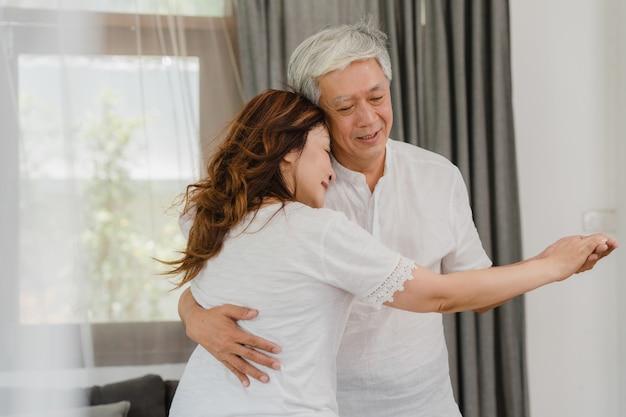 Asiatische ältere paare, die zusammen tanzen, während musik im wohnzimmer zu hause hören, süßes paar genießen liebesmoment beim haben des spaßes, wenn sie zu hause entspannt werden. ältere familie des lebensstils entspannen sich zu hause konzept. Kostenlose Fotos