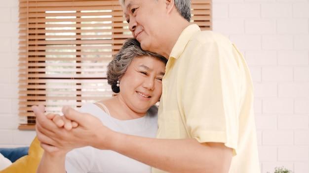 Asiatische ältere paare, die zusammen tanzen, während musik zu hause im wohnzimmer, süße paare hören, genießen liebesmoment beim haben von spaß, wenn sie zu hause entspannt werden. Kostenlose Fotos