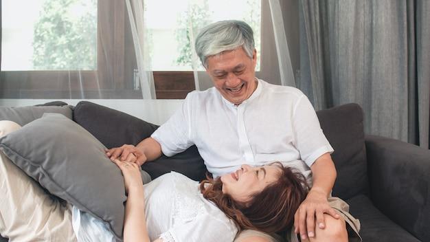 Asiatische ältere paare entspannen sich zu hause. asiatische ältere chinesische großeltern, glückliche lächelnumarmung des ehemanns legen sich ihren frauschoss beim auf sofa im konzept des wohnzimmers zu hause liegen hin. Kostenlose Fotos